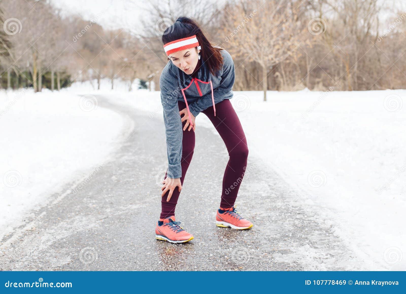 Młodej kobiety uczucia ból w nogach po jogging outside w zima parku