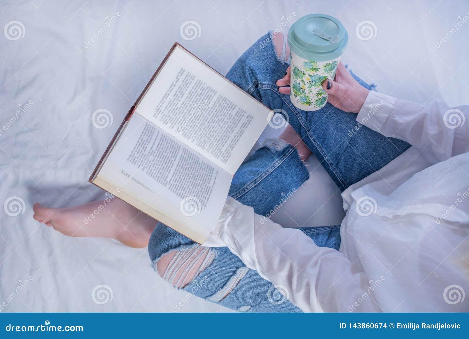 Młodej studenckiej dziewczyny czytelnicza książka w wygodnym łóżku i mienie rezerwujemy na nogach z nagimi ciekami i pić gorącą k