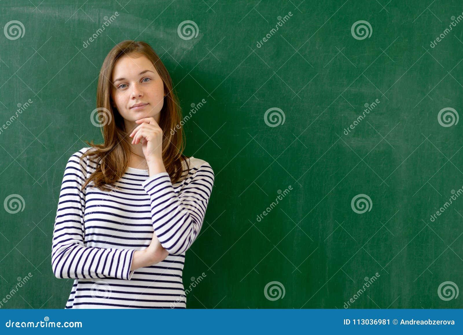 Młodej ufnej uśmiechniętej żeńskiej szkoły średniej studencka pozycja przed chalkboard w sala lekcyjnej
