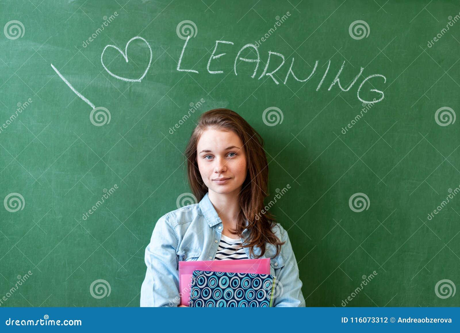 Młodej ufnej uśmiechniętej żeńskiej szkoły średniej studencka pozycja przed chalkboard w sala lekcyjnej, mienie podręczniki
