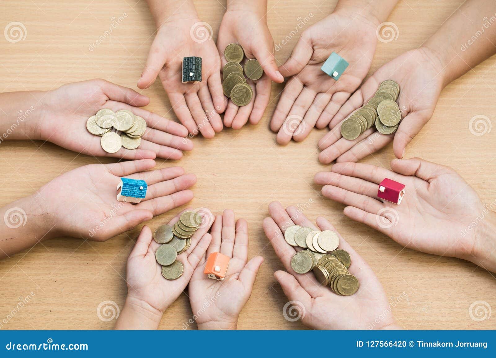 Młodości przedstawienia ręka trzyma wzorcowego dom i drewniany bac moneta