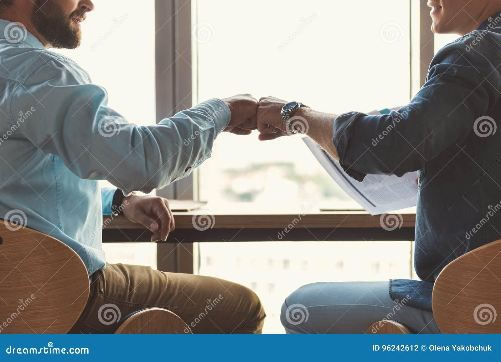 Młodociani faceci komunikuje wpólnie podczas gdy pracujący w biurze