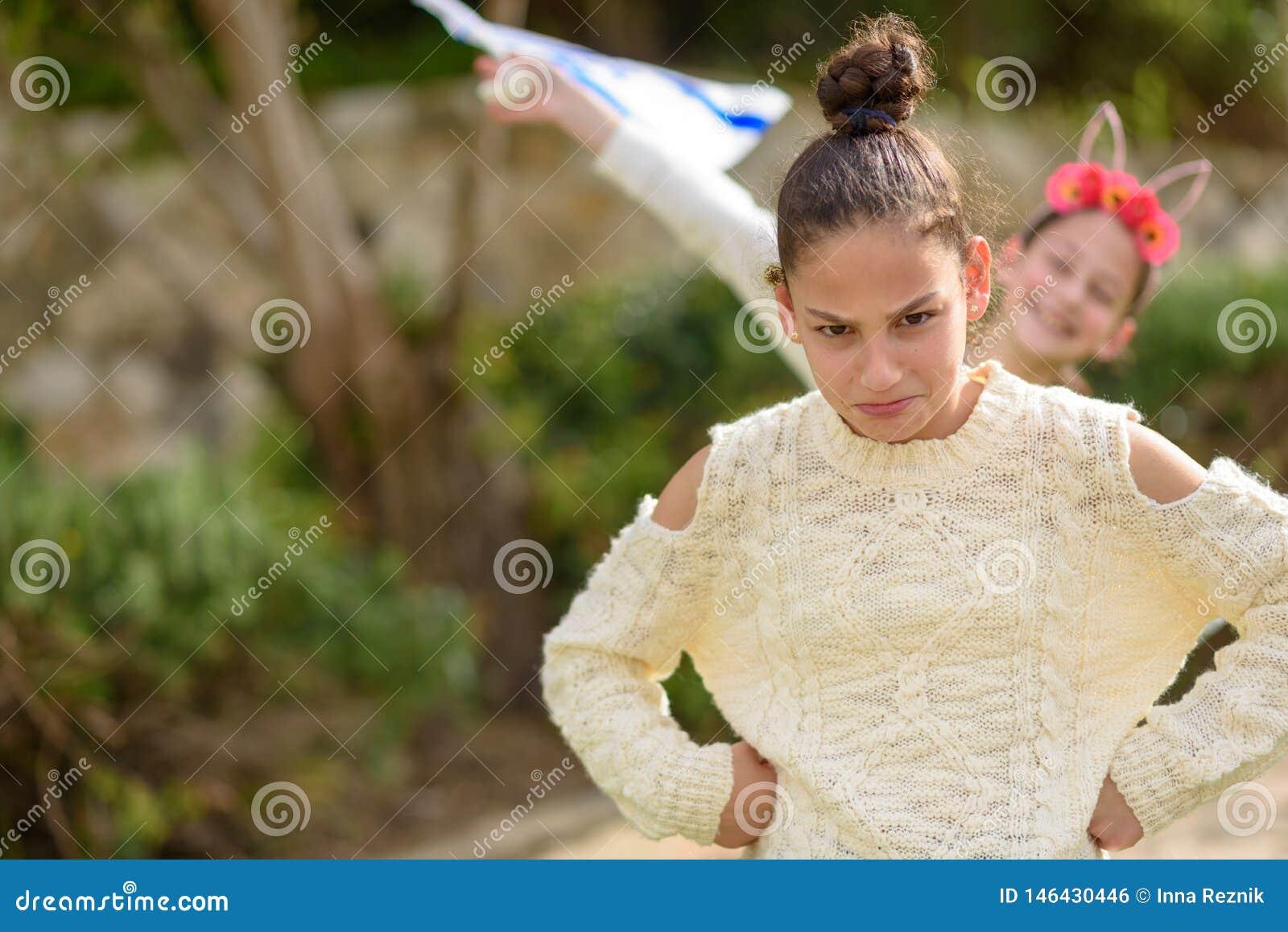 Młody śmieszny nastolatek dziewczyny stać plenerowy z rękami akimbo