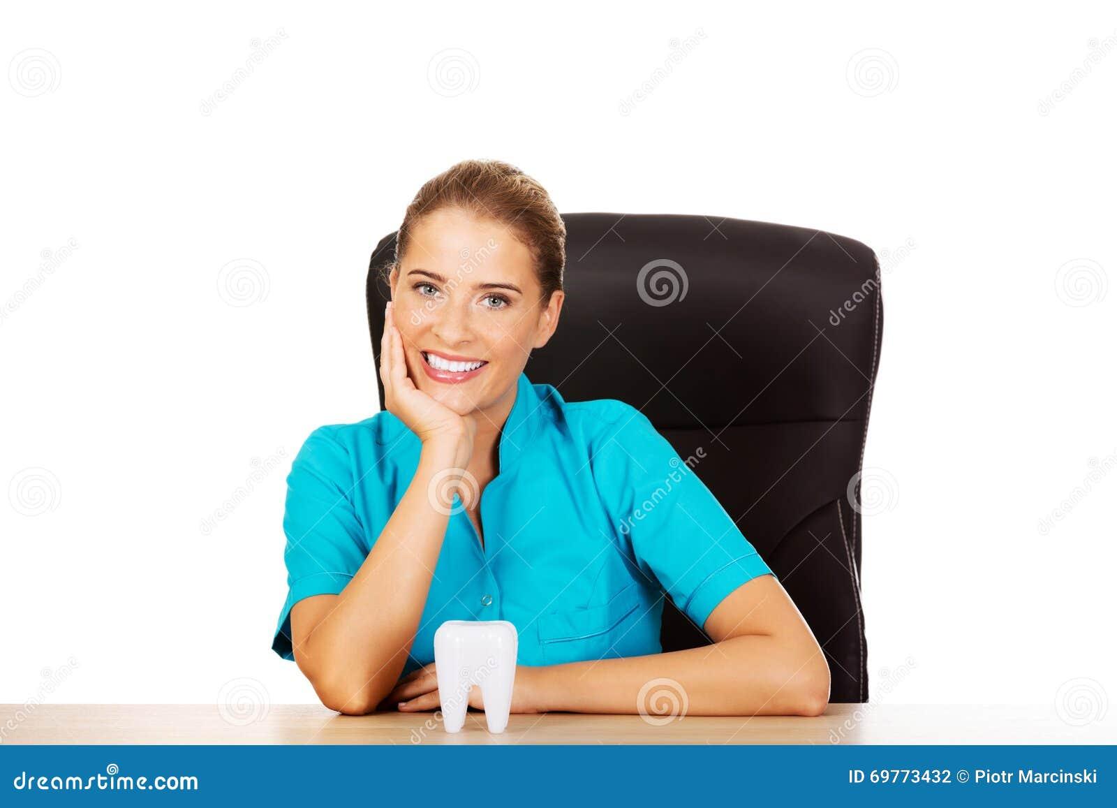 Młody żeński dentysty mienia zębu model i obsiadanie za biurkiem