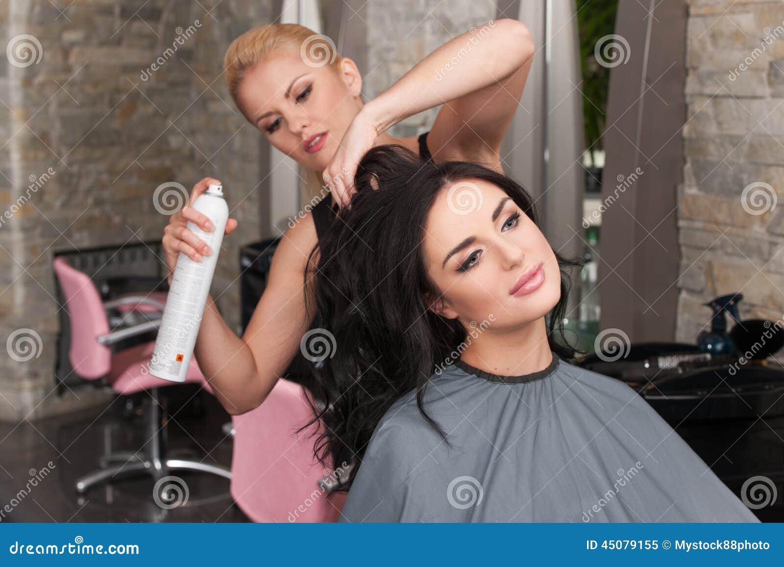 Młody żeński fryzjer stosuje kiść na klienta włosy