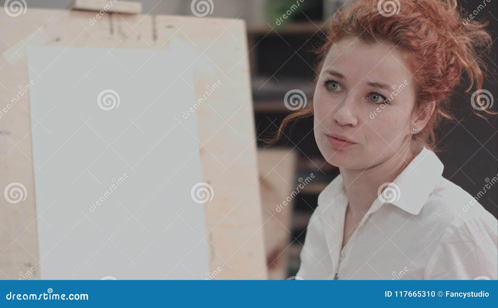 Młody żeński malarz blisko sztalugi opisuje kreatywnie proces