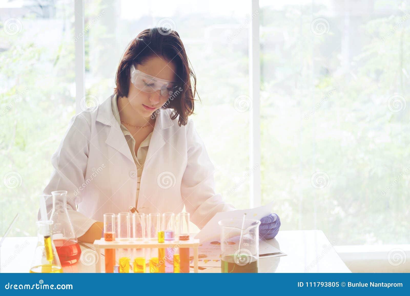 Młody żeński naukowiec w lab pracowniku robi badania medyczne wewnątrz