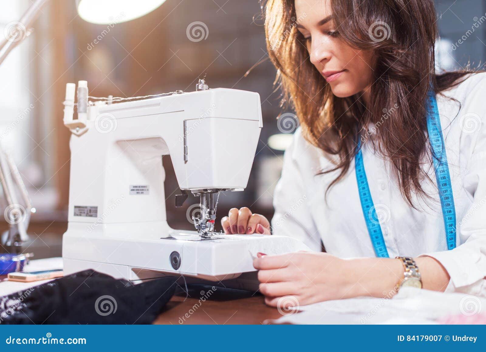 Młody żeński projektant mody pracuje na szwalnej maszynie w warsztacie