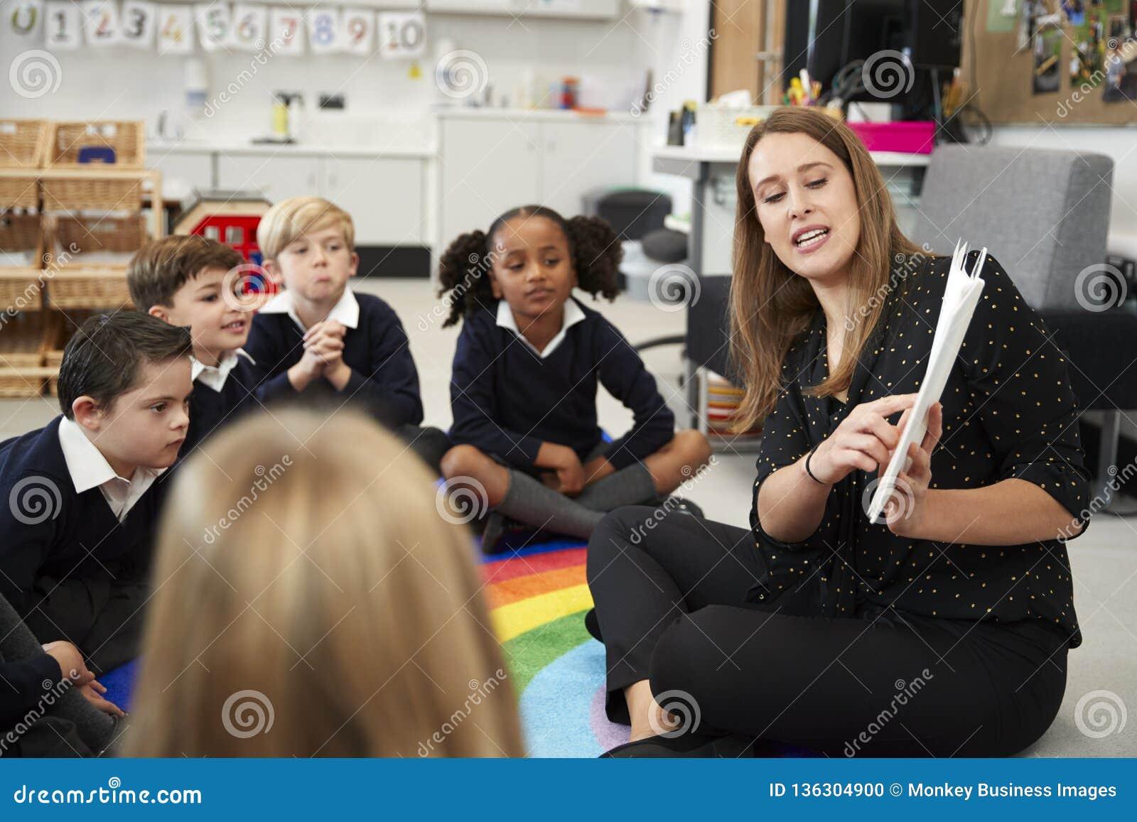 Młody żeński szkoła podstawowa nauczyciel czyta książkę dzieci siedzi na podłodze w sali lekcyjnej, selekcyjna ostrość