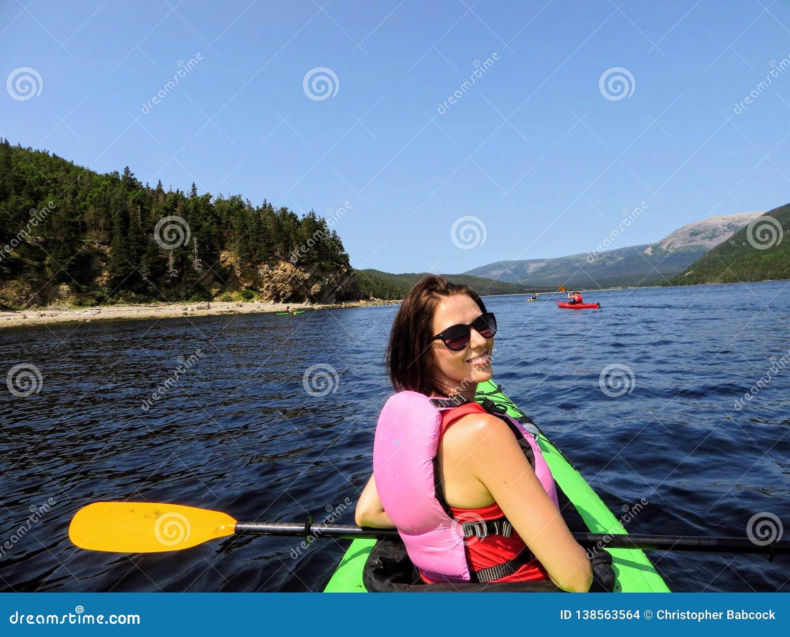 Młody żeński turysta bada piękne wody w Bonne w kajaku Trzymać na dystans z grupą kakayers, w Gros Morne
