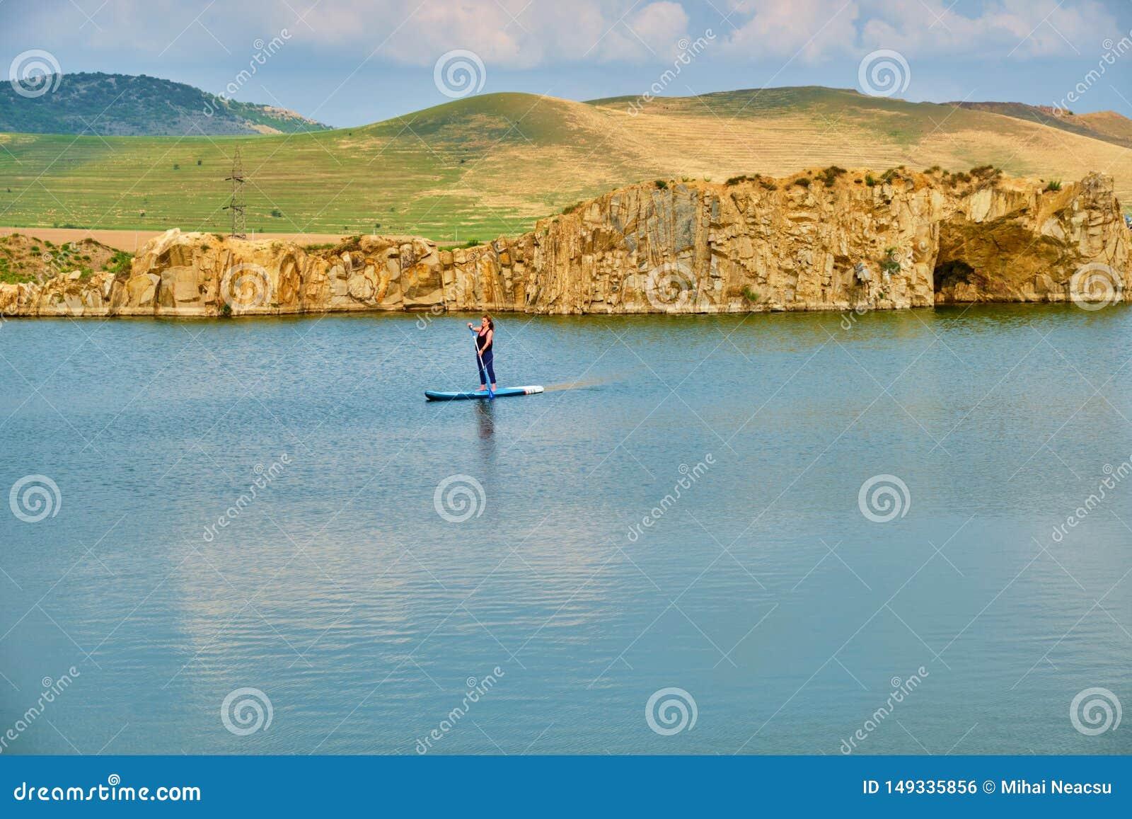 Młody żeński turystyczny abordaż na odosobnionym jeziorze z przestrzenią dla teksta przy dnem, Iacobdeal jezioro w Turcoaia, Tulc