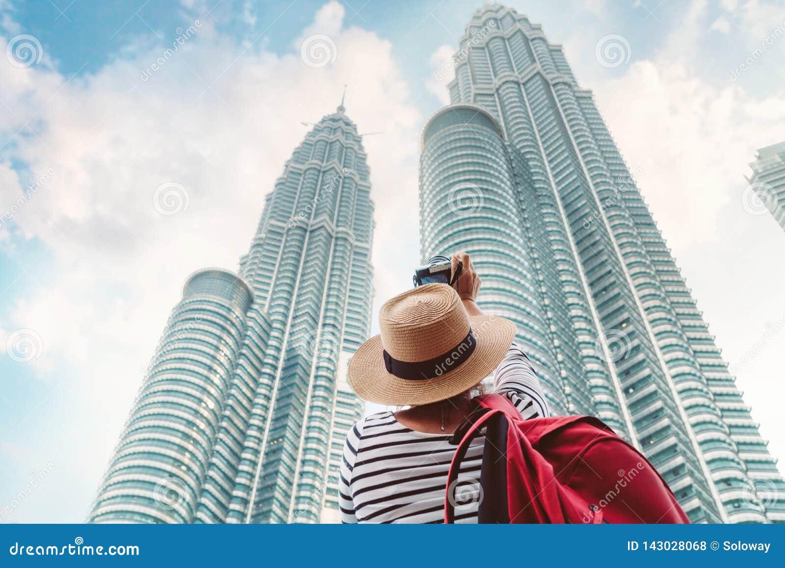 Młody żeński turystyczny robi obrazka strzał dwa drapacz chmur góruje w dużym azjatykcim mieście