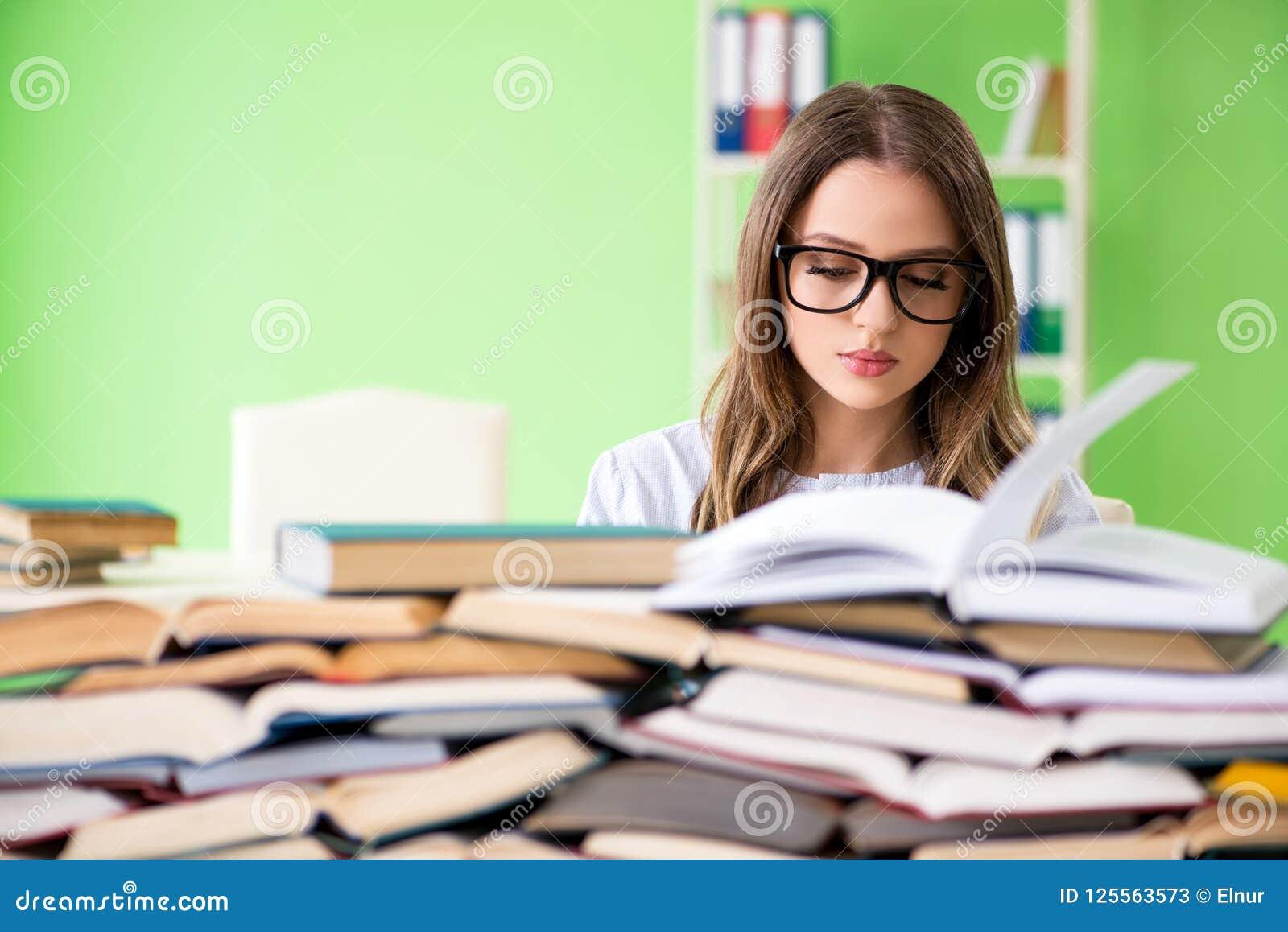 Młody żeńskiego ucznia narządzanie dla egzaminów z wiele książkami