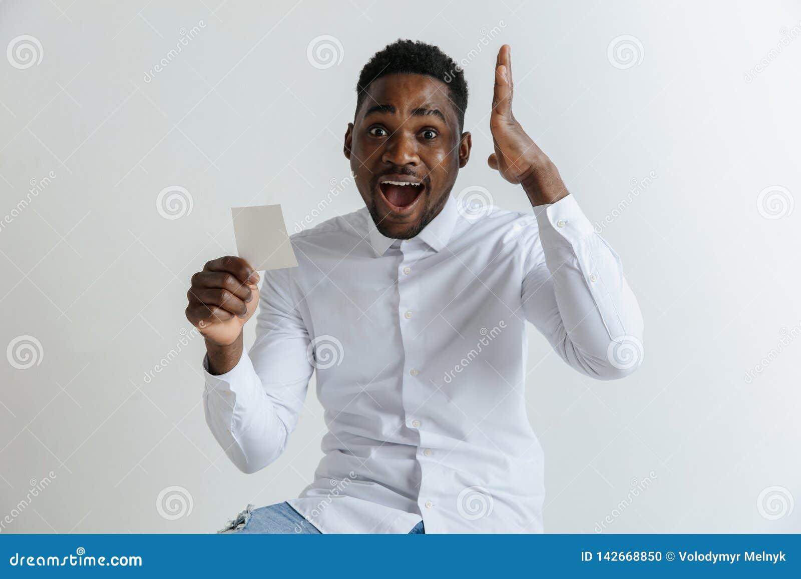 Młody afro mężczyzna z zdziwionym szczęśliwym wyrażeniem wygrywał zakład na szarym pracownianym tle