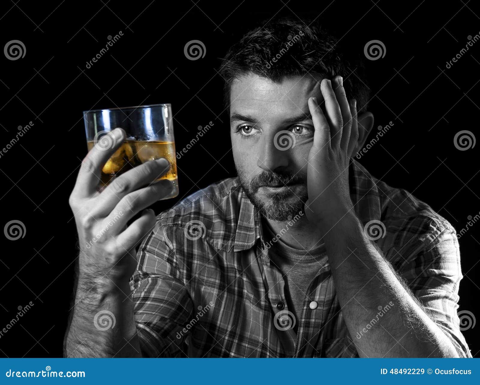 Młody alkoholiczny nałogowa mężczyzna pijący z whisky szkłem w alkoholizmu pojęciu