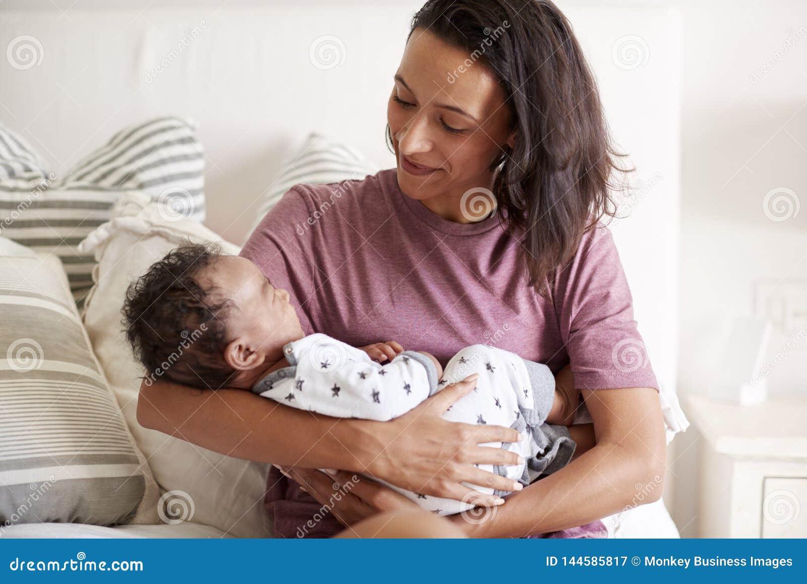 Młody amerykanin afrykańskiego pochodzenia dorosłego matki obsiadanie na jej mieniu i łóżku jej dziecko syn w jej rękach, talia w