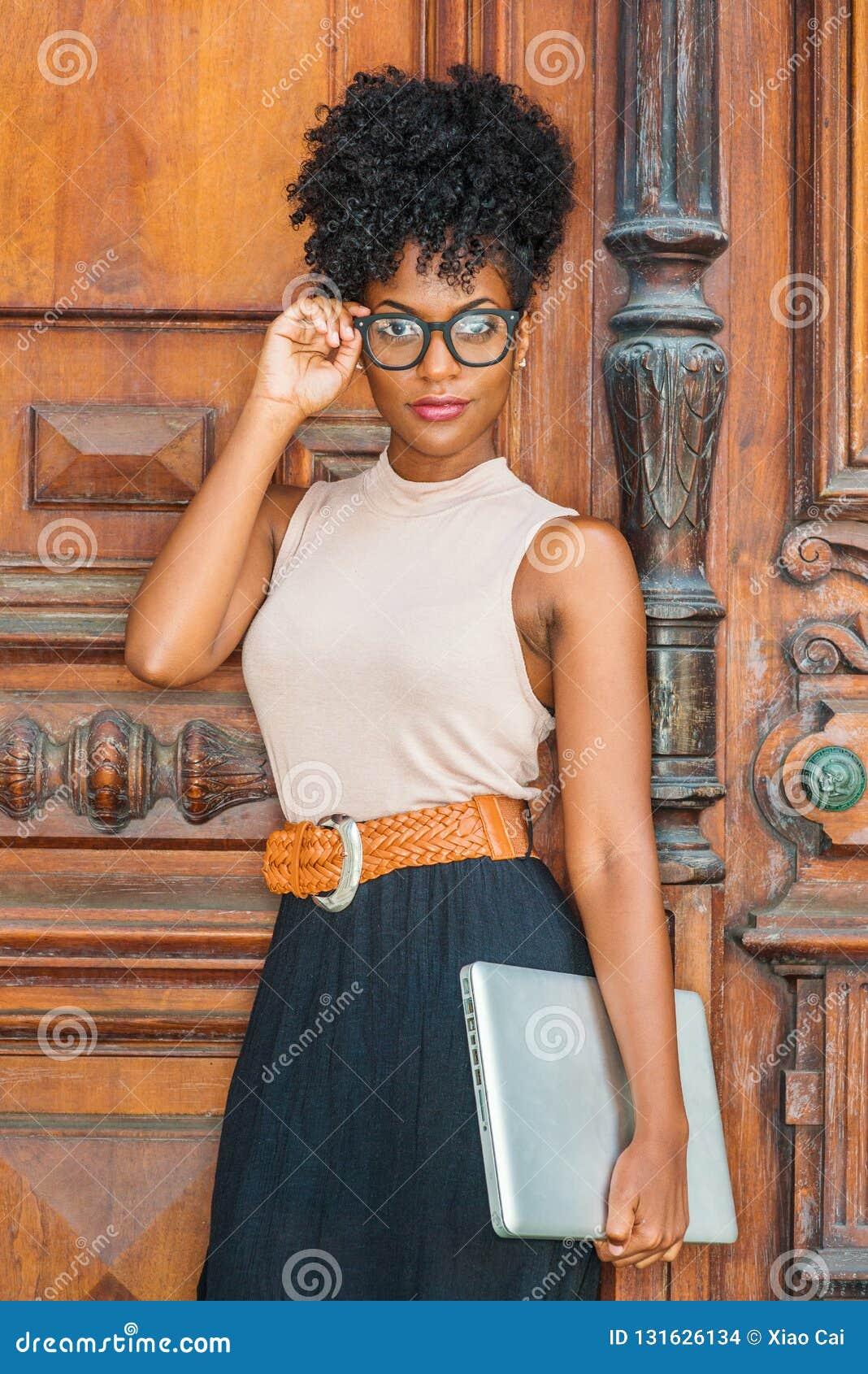 Młody amerykanin afrykańskiego pochodzenia student collegu z afro fryzurą, oczu szkła, jest ubranym sleeveless lekkiego koloru wi