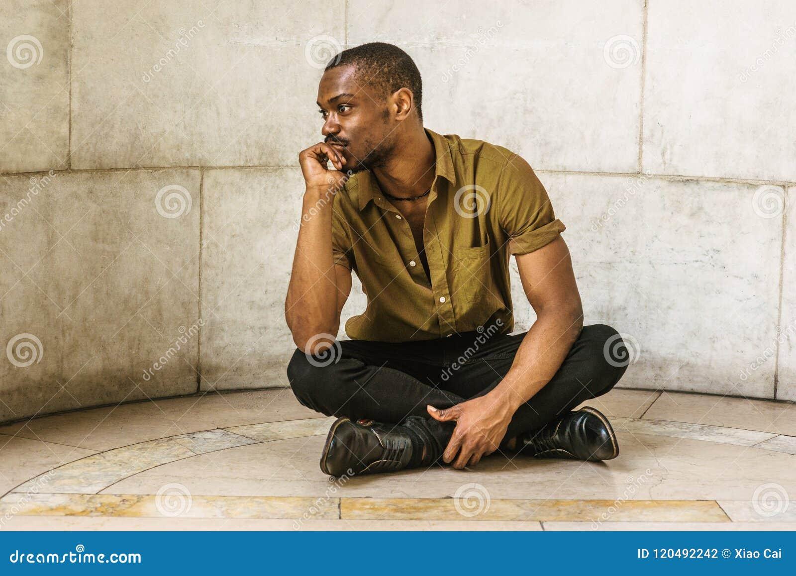 Młody amerykanina afrykańskiego pochodzenia mężczyzna obsiadanie na ziemi w Nowy Jork, thinki