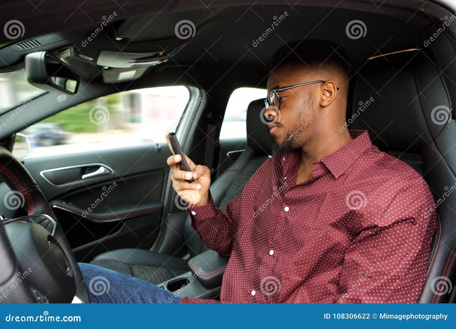 Młody amerykanina afrykańskiego pochodzenia mężczyzna patrzeje telefon komórkowego przed jechać w samochodzie