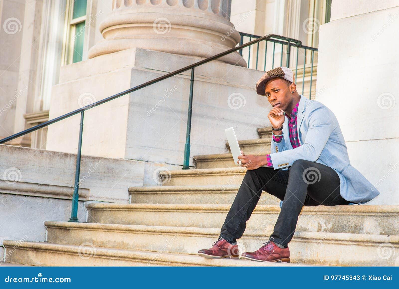 Młody amerykanina afrykańskiego pochodzenia mężczyzna pracuje na laptopie outside wewnątrz