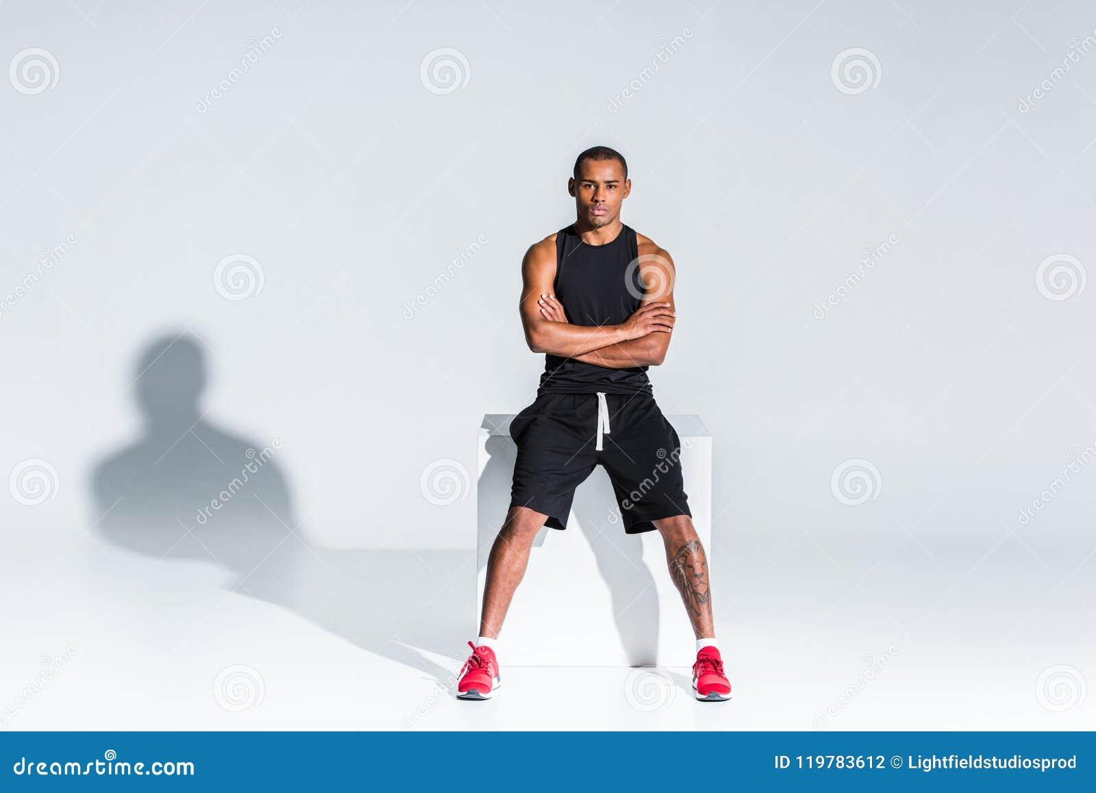 Młody amerykanina afrykańskiego pochodzenia sportowiec siedzi kamerę i patrzeje z krzyżować rękami