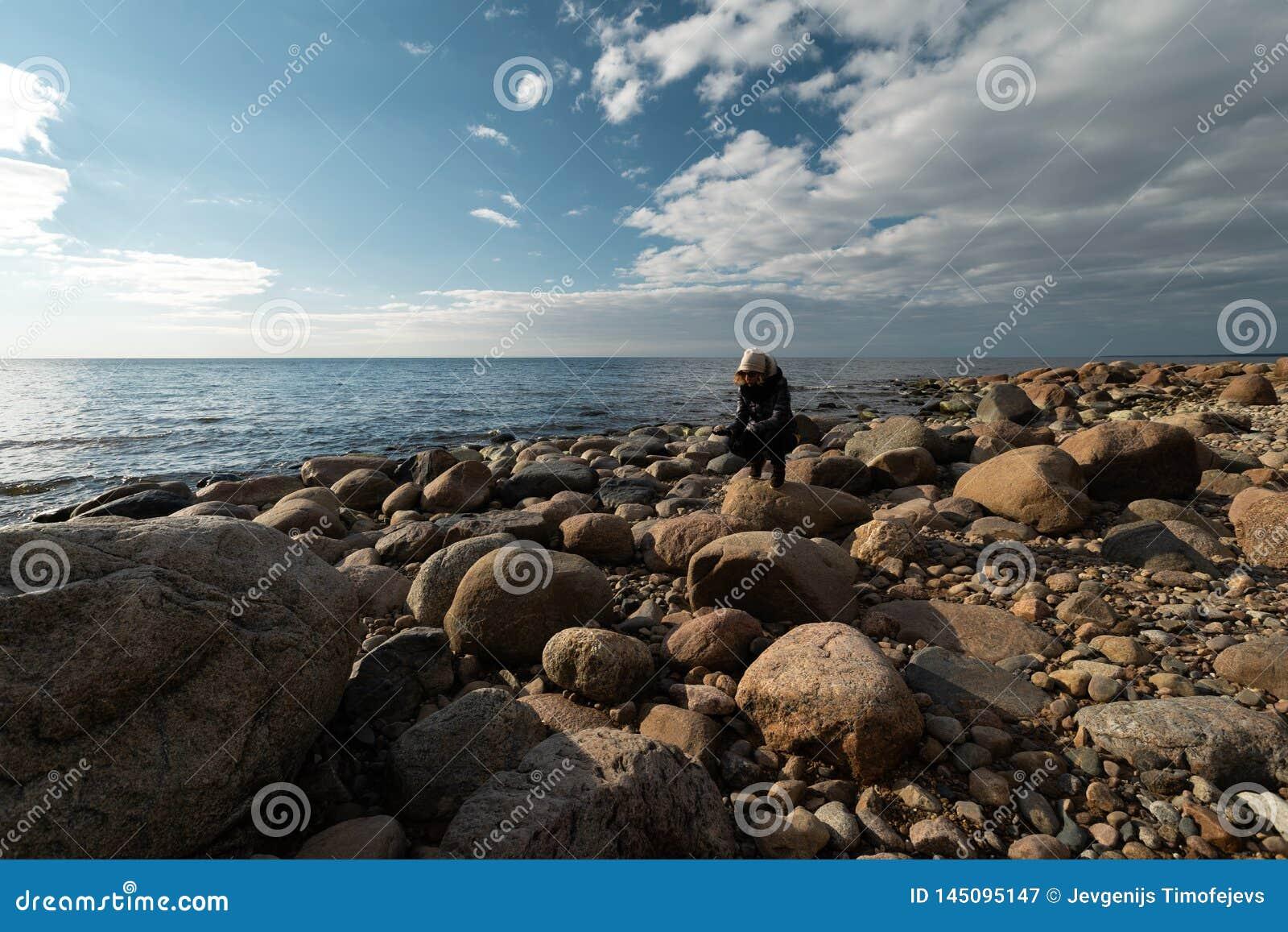 Młody archeolog na głazu plażowym szuka egzocie kołysa na linii brzegowej morze bałtyckie