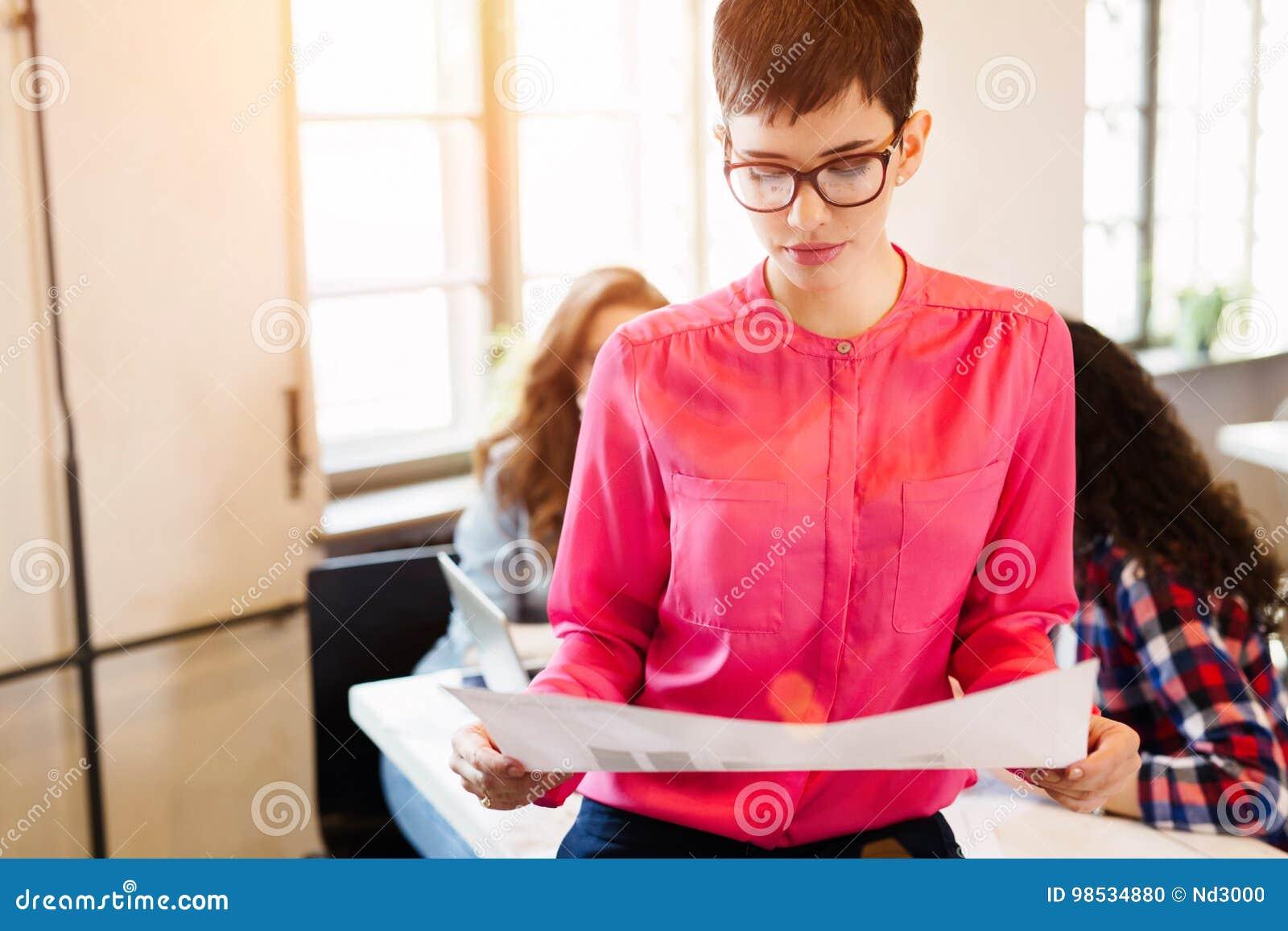 Młody atrakcyjny żeński projektant patrzeje projekta plan