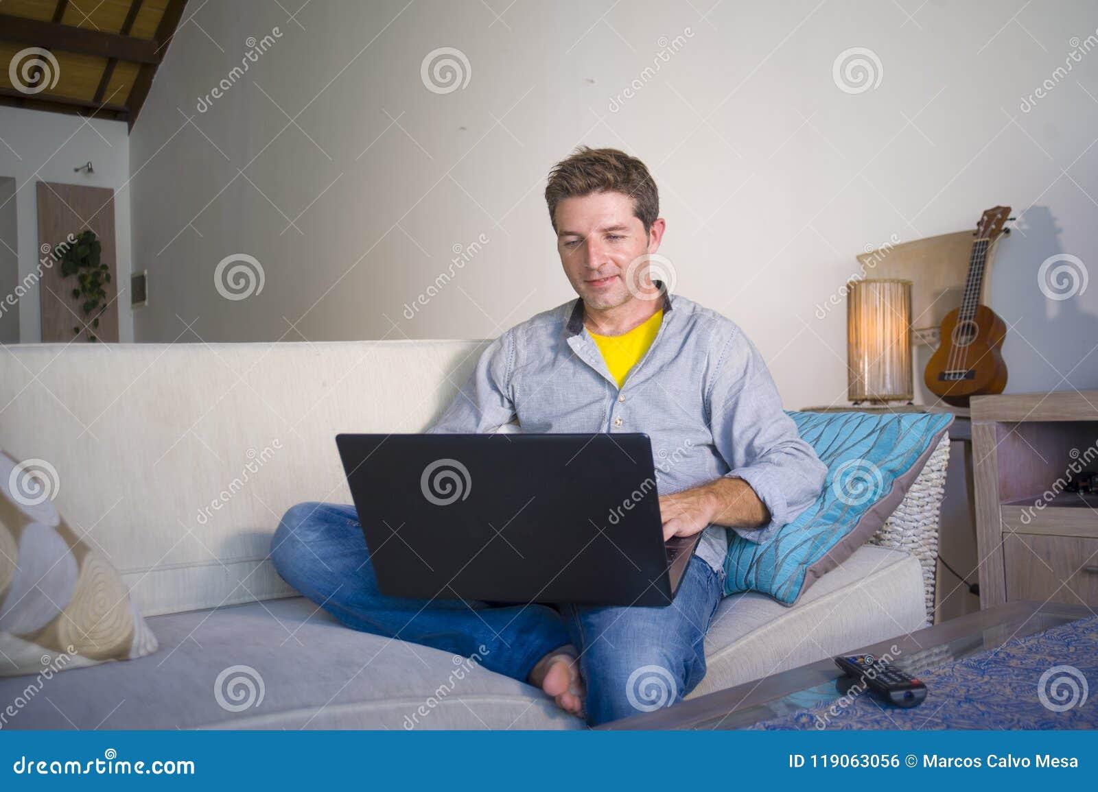 Młody atrakcyjny i pomyślny mężczyzna pracuje od domowego żywego izbowego obsiadania na leżanka networking na laptopie szczęśliwy