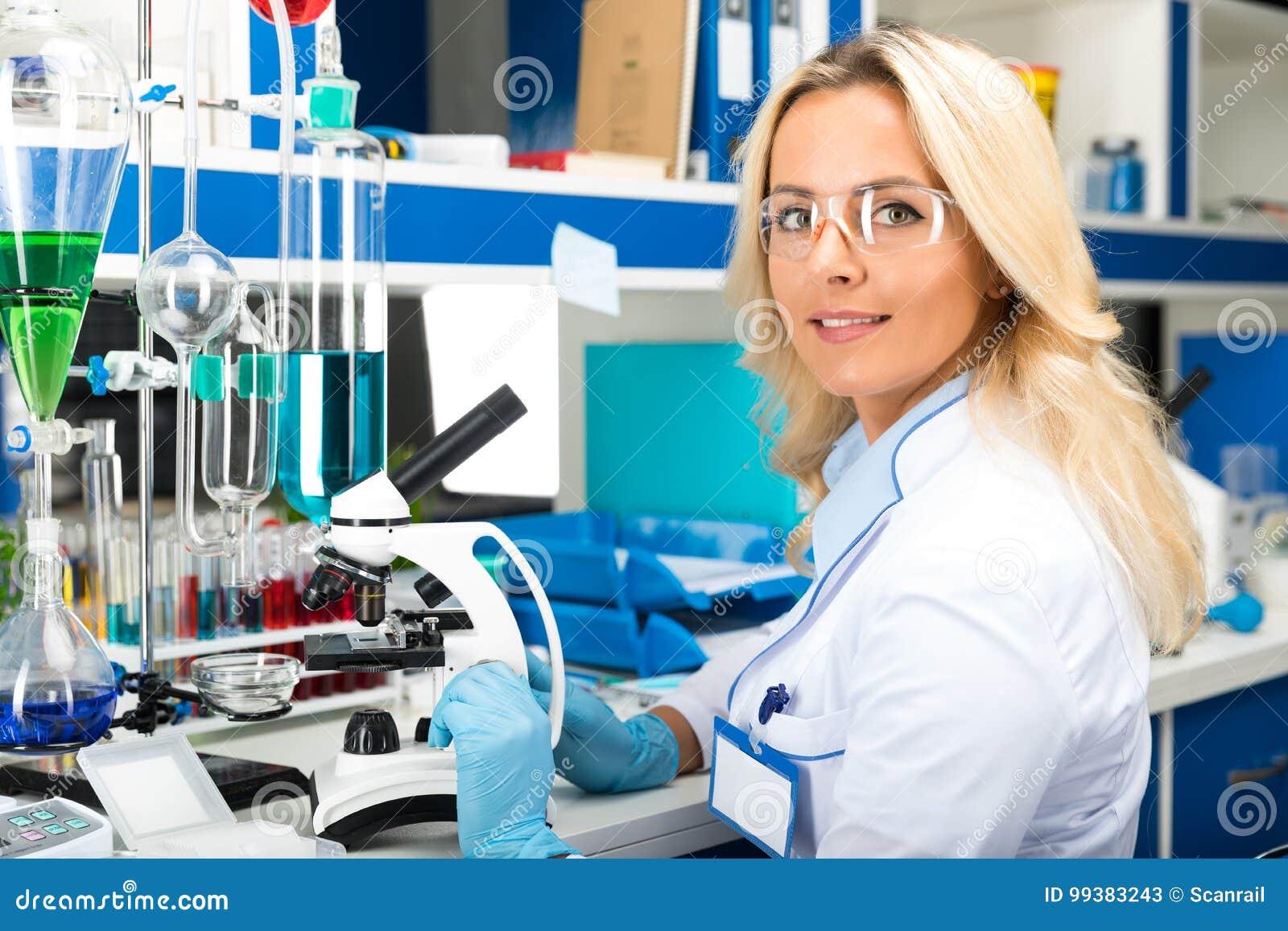 Młody atrakcyjny kobieta naukowiec bada w laboratorium