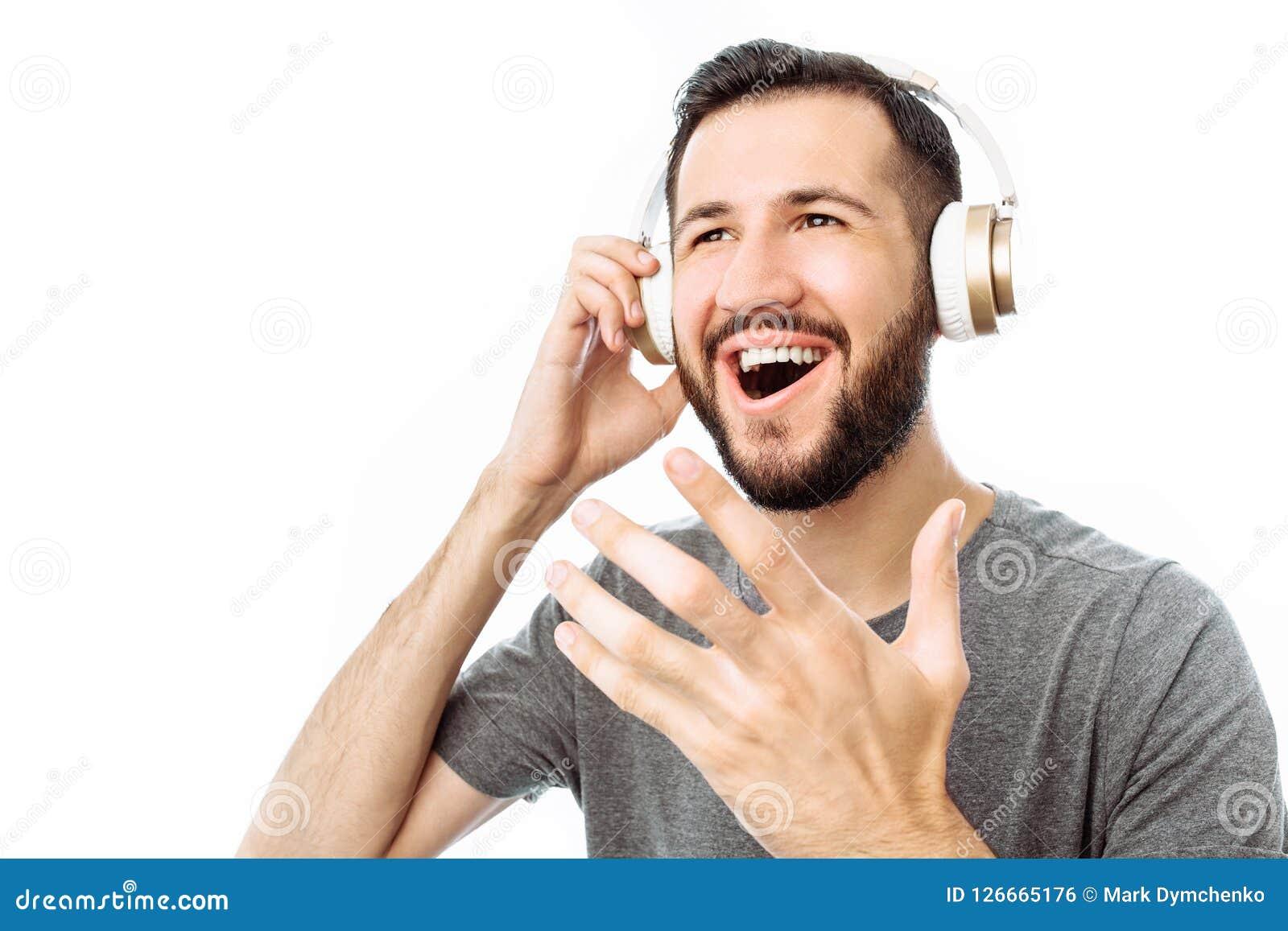 Młody atrakcyjny mężczyzna śpiewa i słucha muzyka z hełmofonami