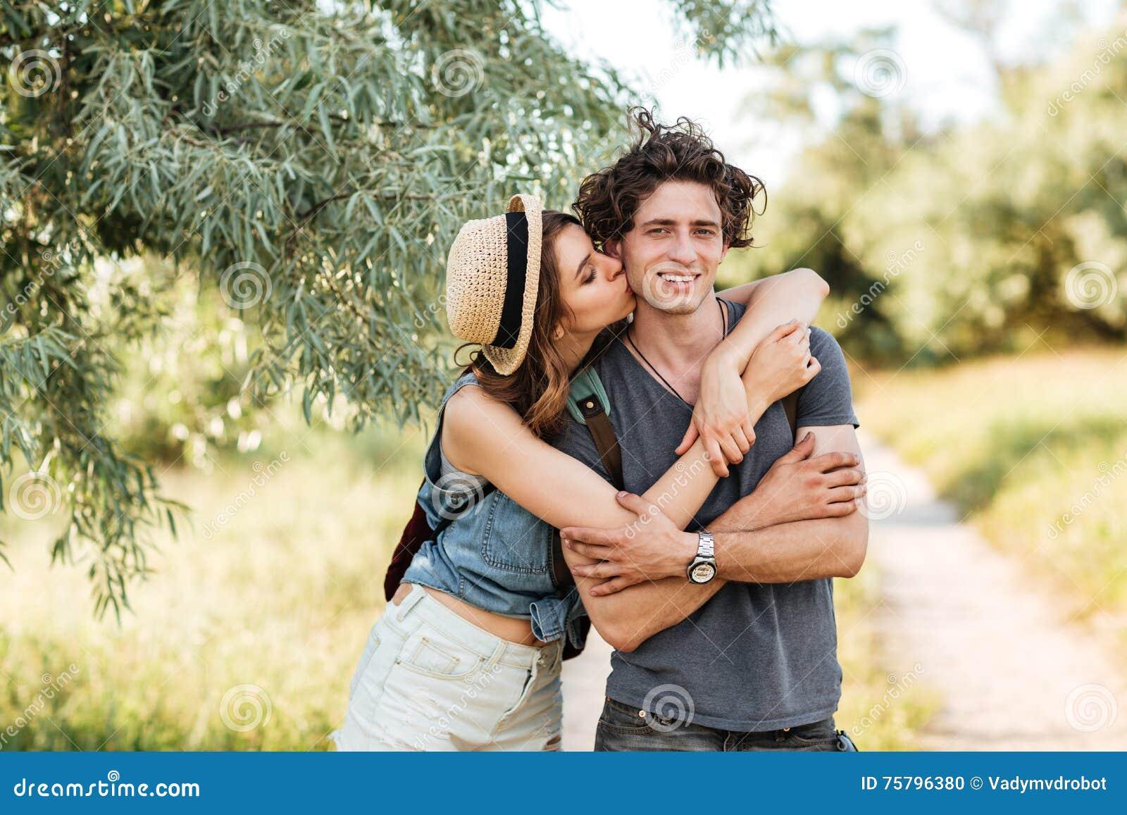 Młody atrakcyjny modniś pary całowanie przy lasowym tłem
