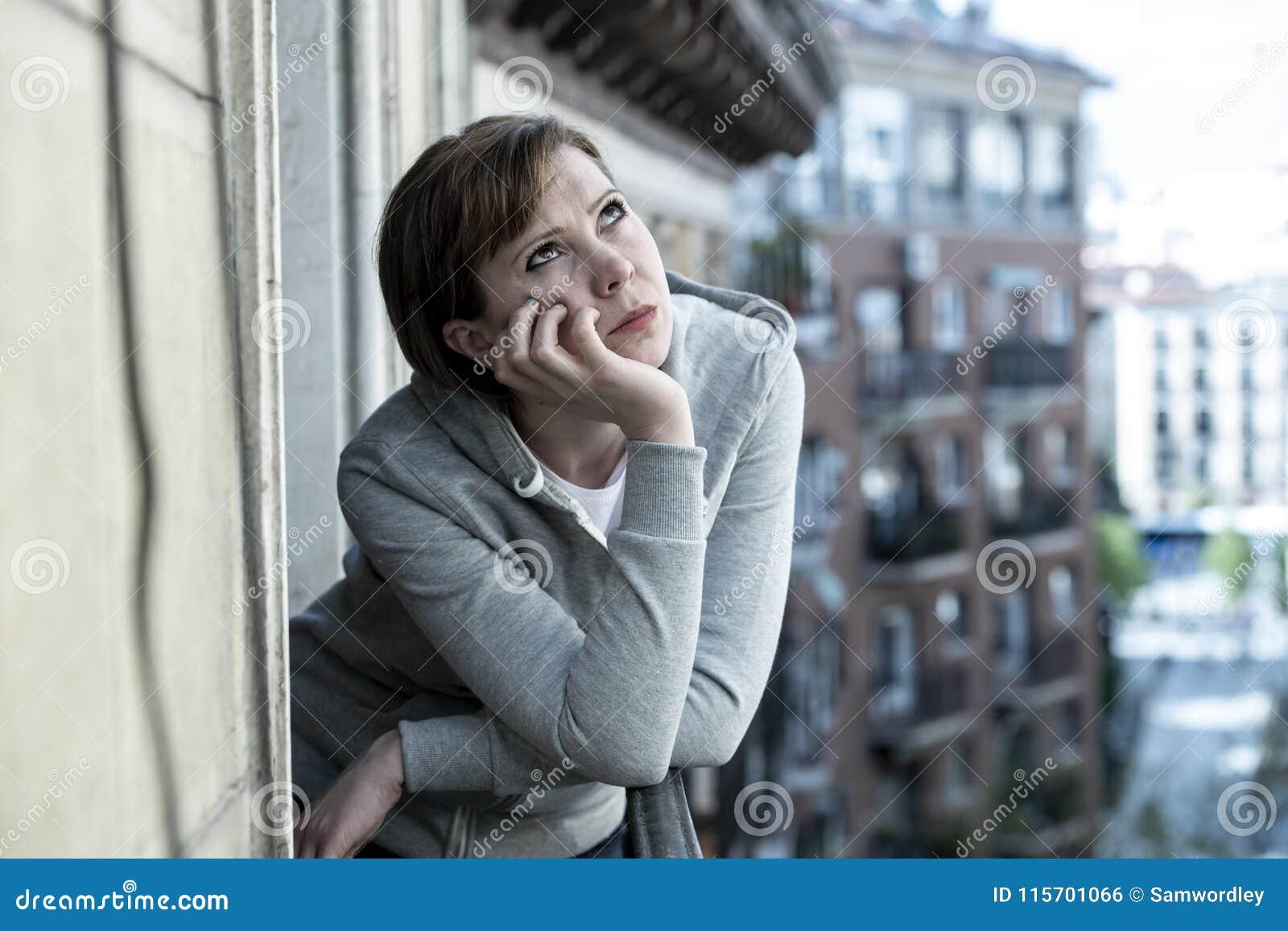 Młody atrakcyjny nieszczęśliwy przygnębiony osamotniony kobiety patrzeć martwił się na balkonie w domu Miastowy widok