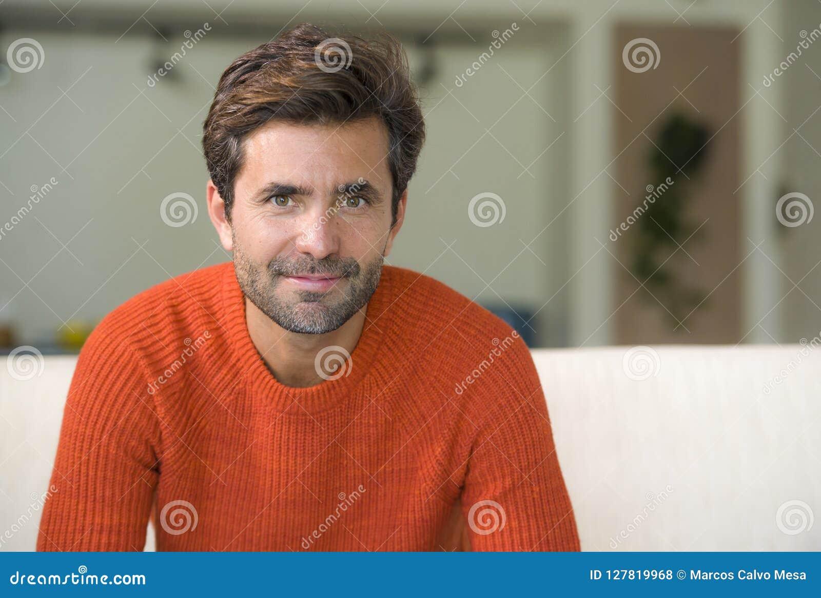 Młody atrakcyjny, szczęśliwy 30s mężczyzna uśmiecha się obsiadanie przy żywą izbową kanapy leżanką w jego nowożytnej mieszkanie o