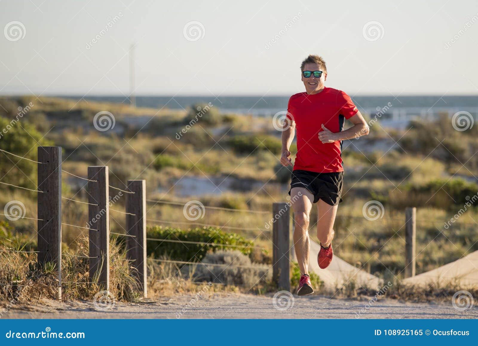 Młody atrakcyjny, szczęśliwy sporta biegacza mężczyzna z zdrowym ciała szkoleniem z na droga śladzie w lato działającym treningu