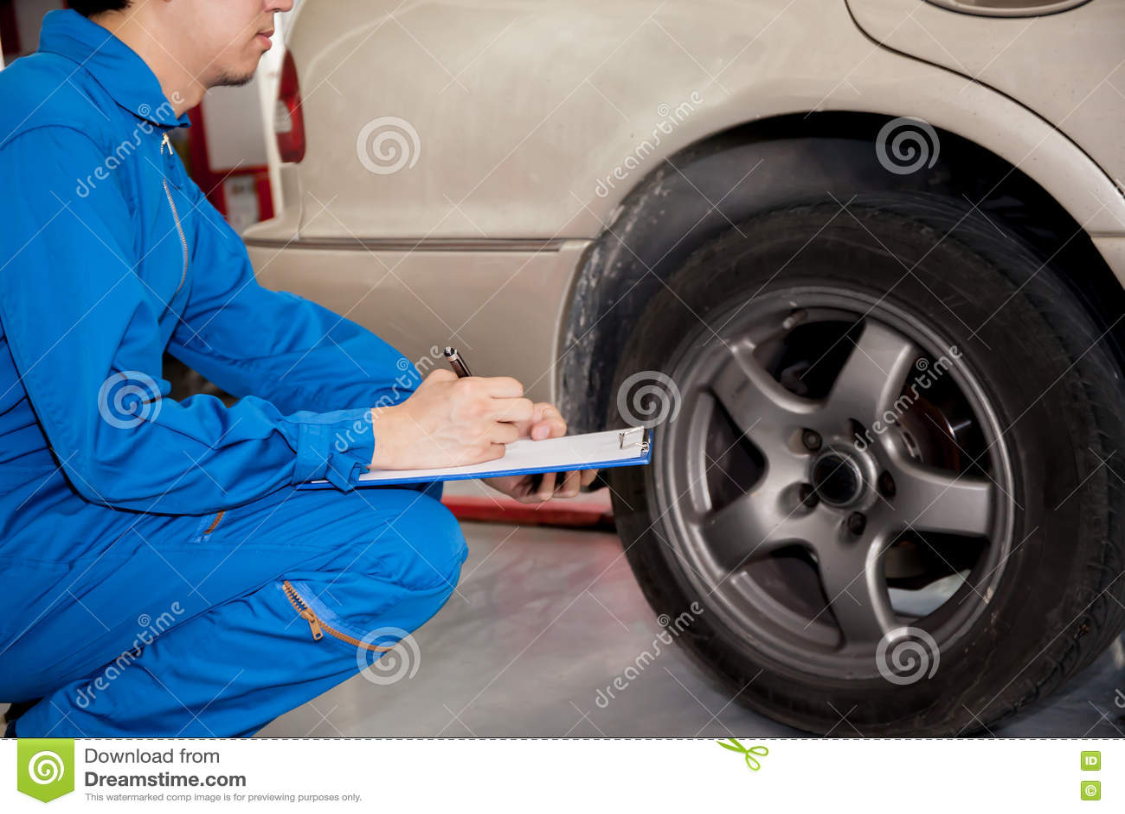 Młody automobilowy technik sprawdza na samochodowych oponach w garażu