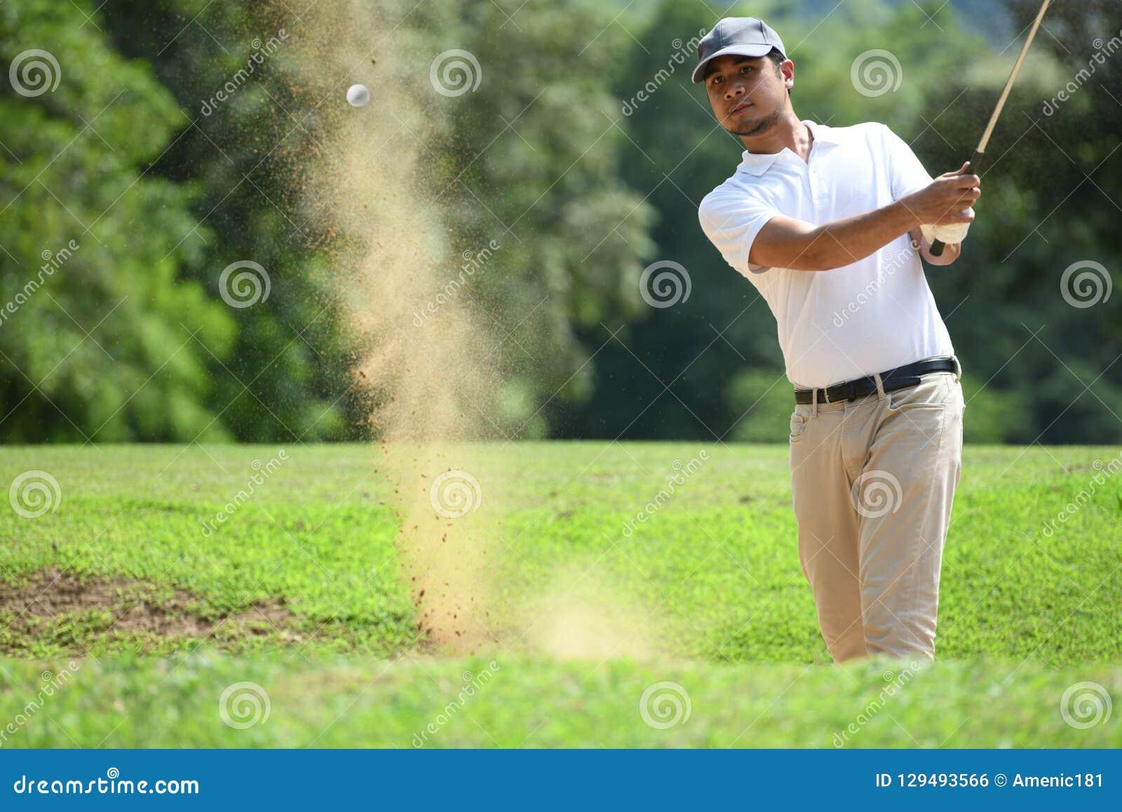 Młody Azjatycki mężczyzna golfista uderza bunkieru strzał