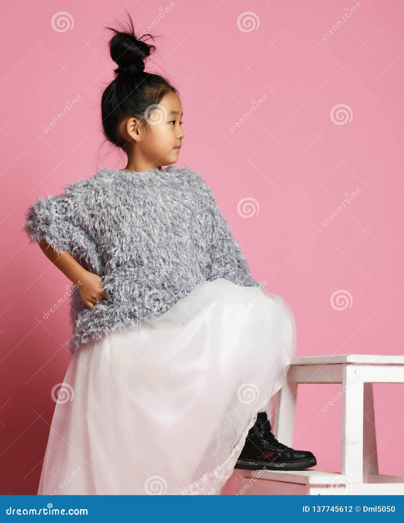 Młody azjatykci dziewczyna dzieciak w długiej biel spódnicie, popielatym puszystym pulowerze i czerń butach z stopą na kroku,