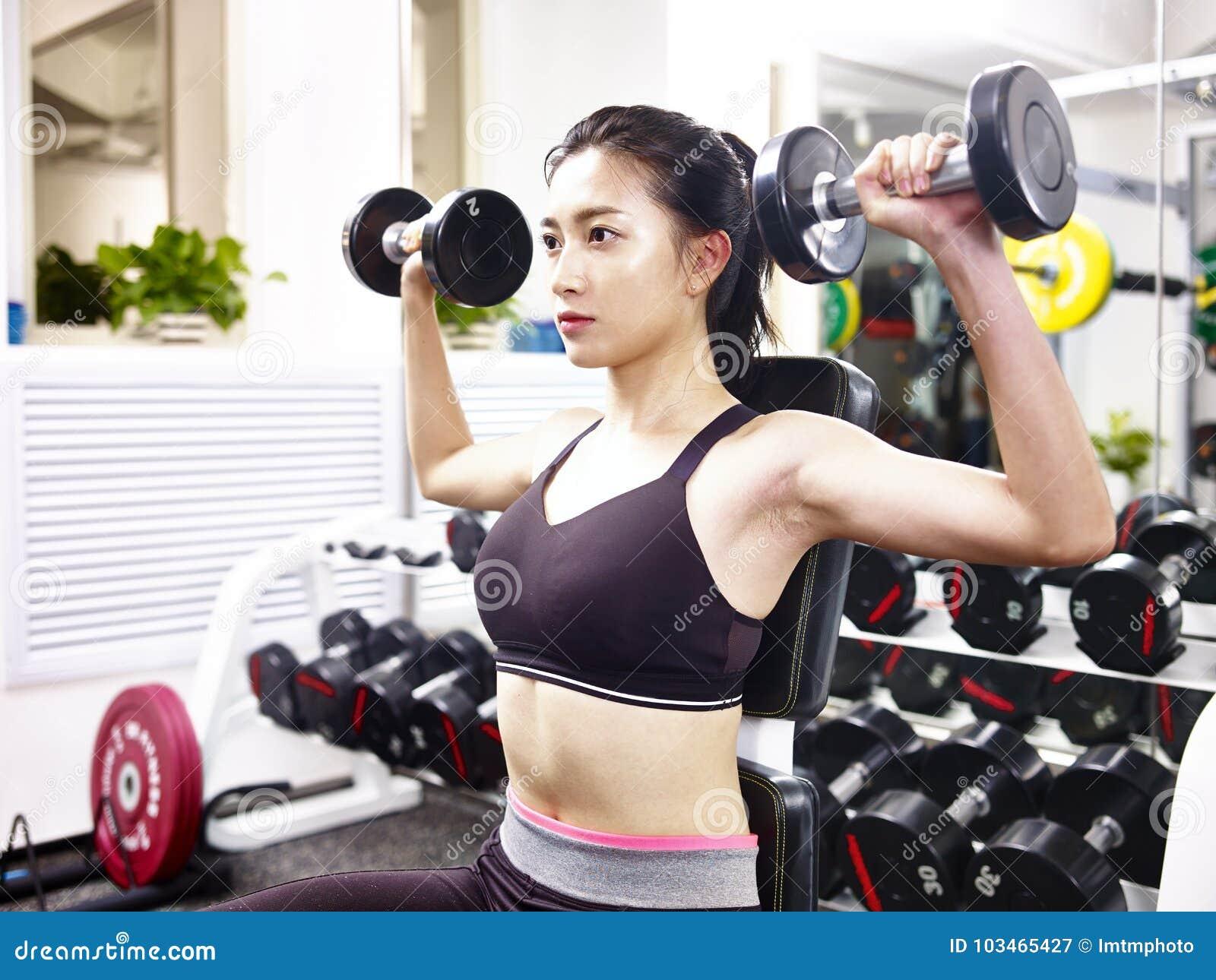 Młody azjatykci kobiety ćwiczyć pracujący w gym out