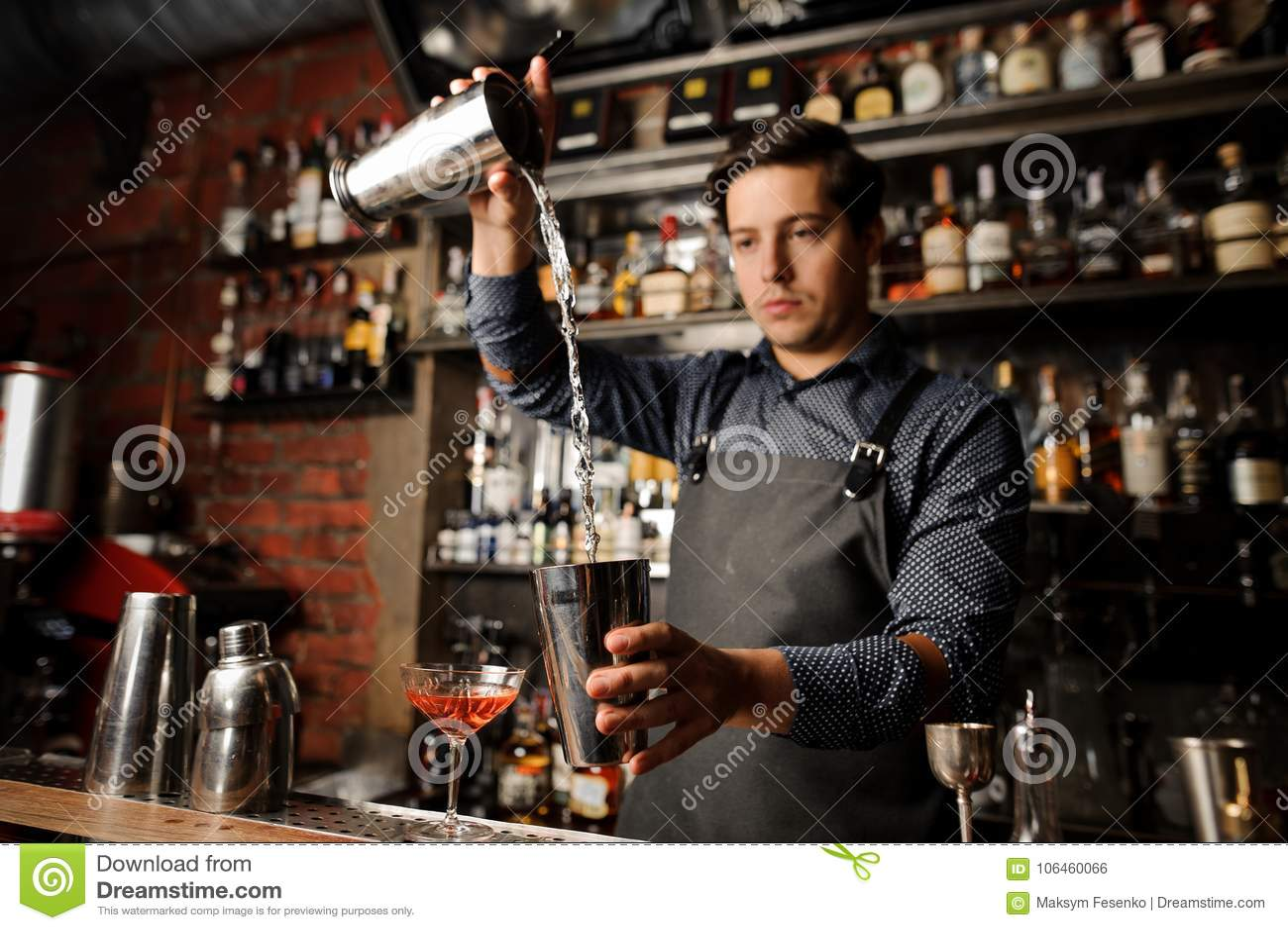 Młody barman nalewa alkoholicznego napój od jeden metalu szkła w inny
