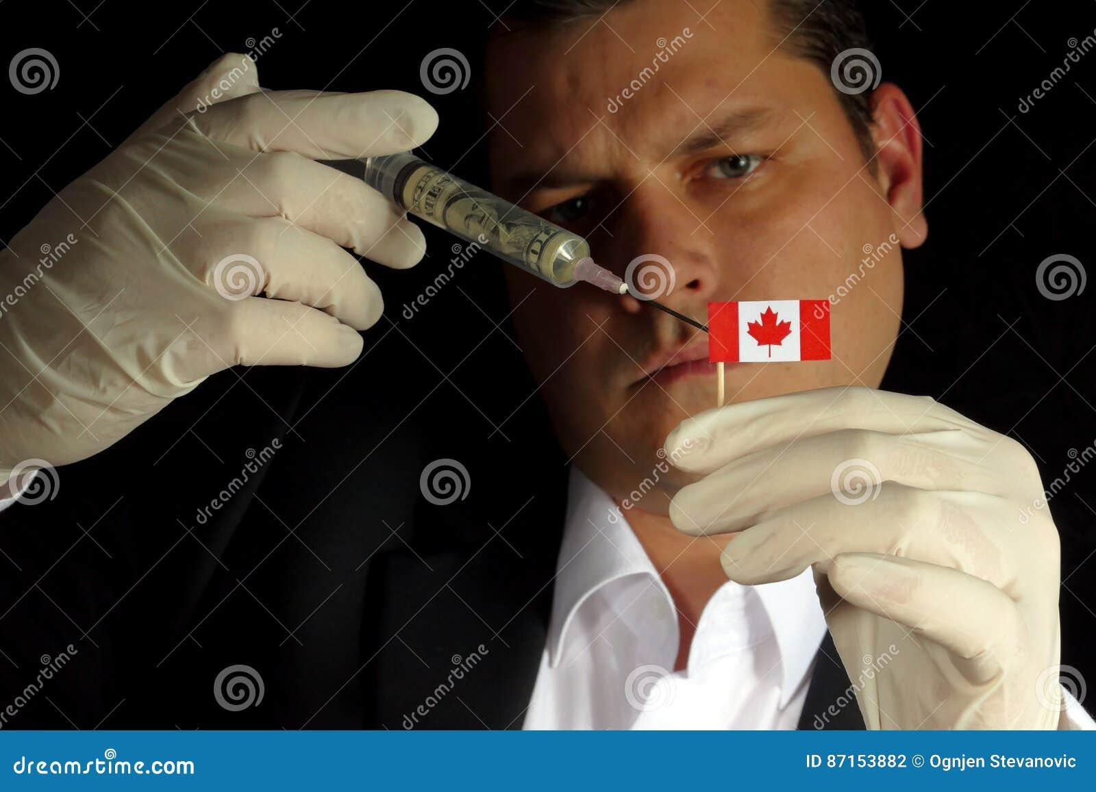 Młody biznesmen daje pieniężnemu zastrzykowi kanadyjczyk flaga