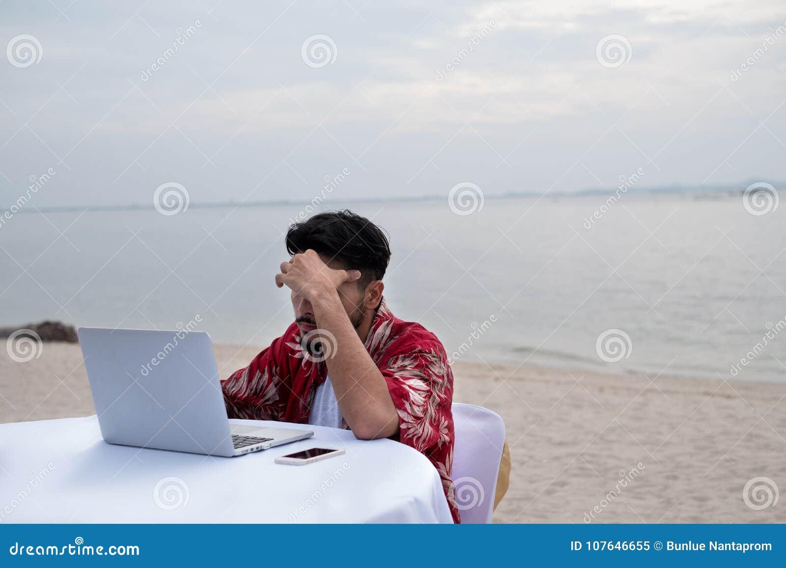 Młody biznesmen pracuje daleko na plaży Biznesmena wor