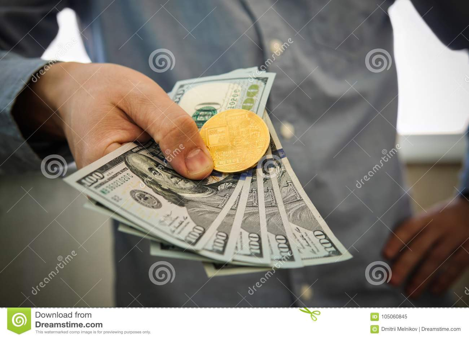 Młody biznesmen trzyma dolara i monetę bitcoin w ręce