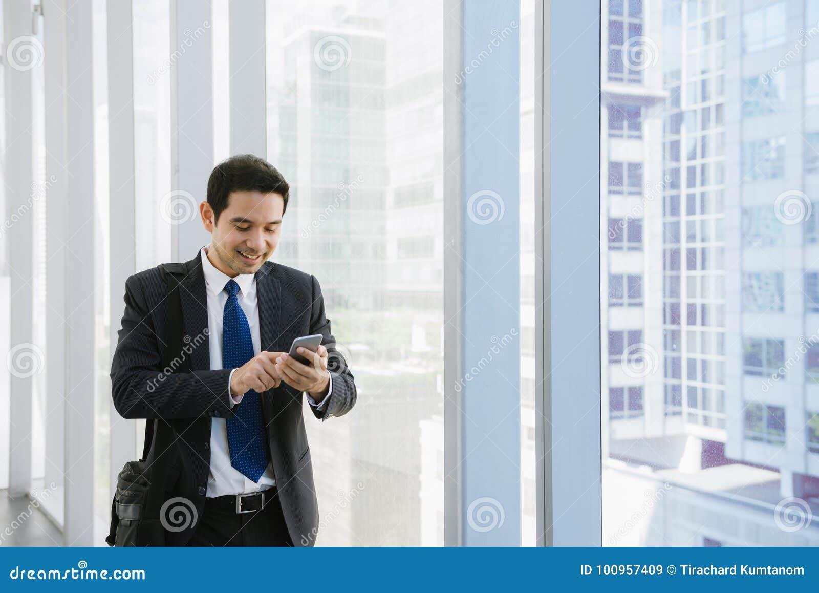 Młody biznesmen w lotnisku Przypadkowy miastowy fachowy biznesowy mężczyzna używa smartphone uśmiecha się szczęśliwego inside bud