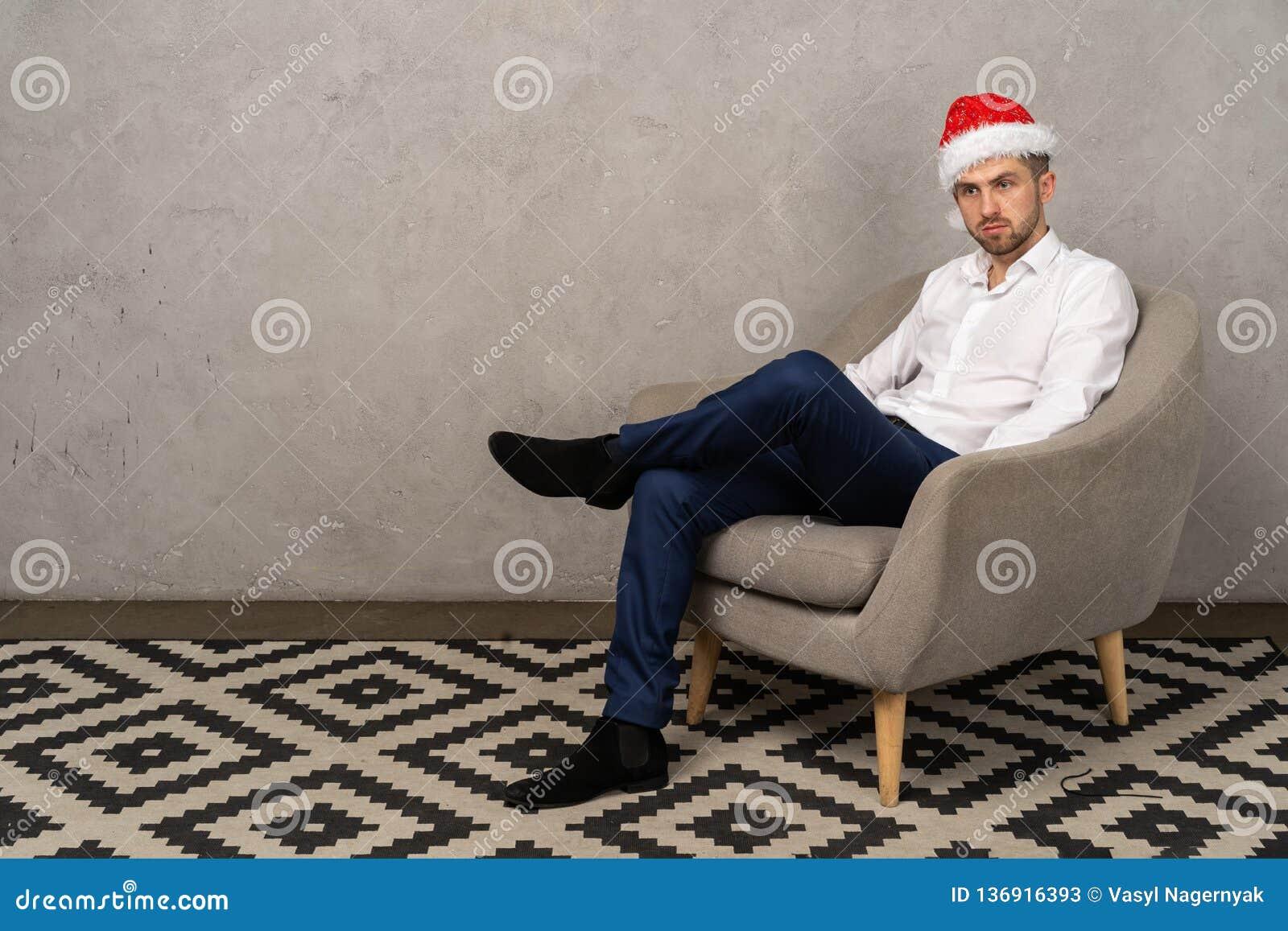 Młody biznesmena obsiadanie na krześle w Santa kapeluszu podczas gdy nudny nowego roku przyjęcie w biurze