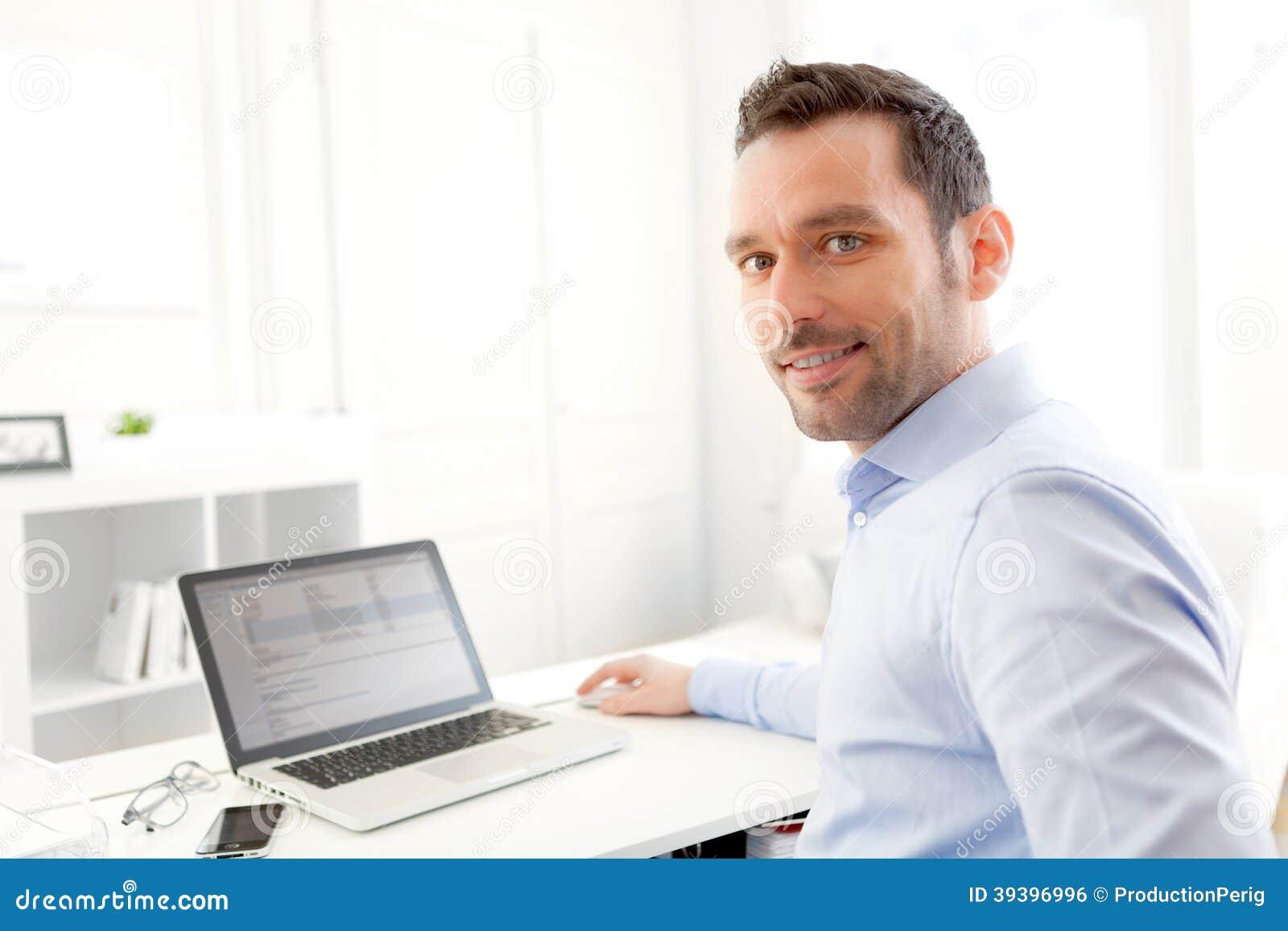 Młody biznesowy mężczyzna pracuje w domu na jego laptopie