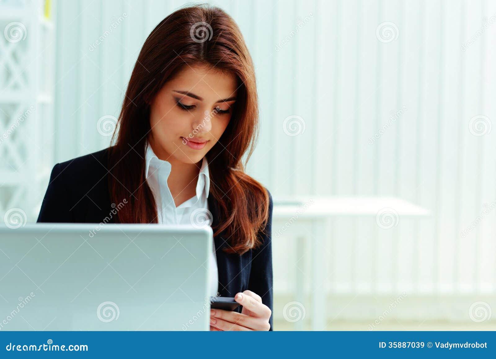 Młody bizneswoman patrzeje smartphone