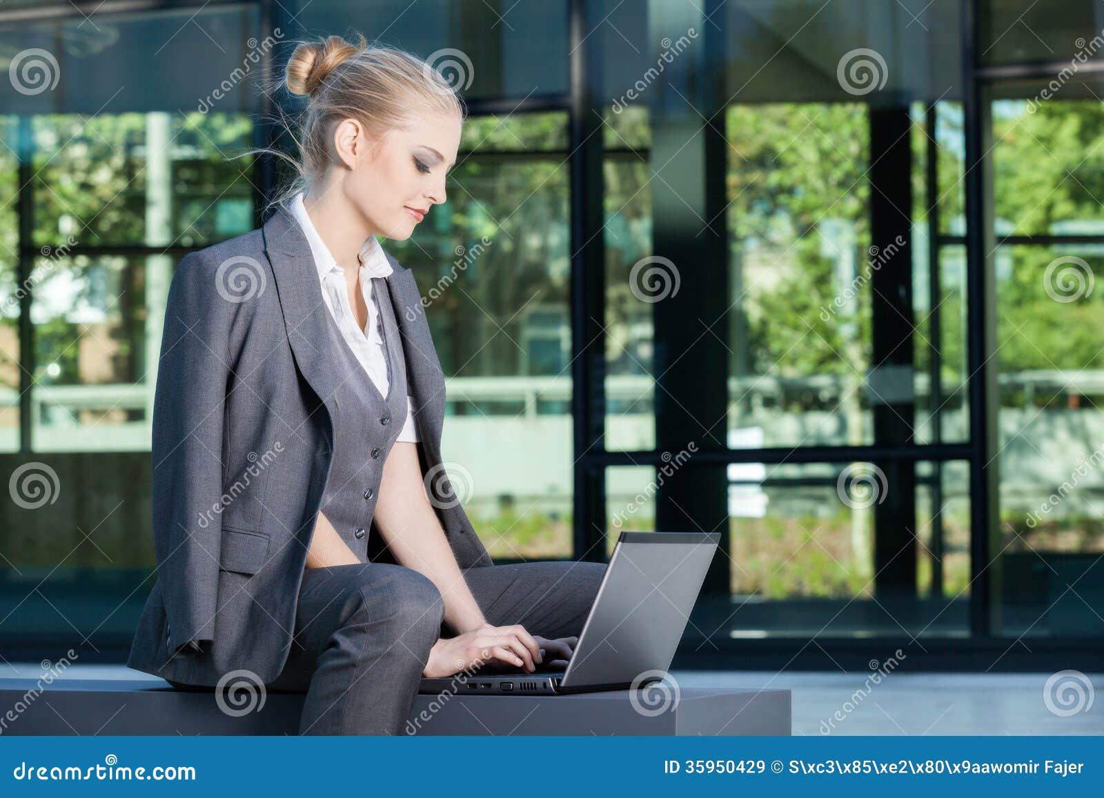Młody bizneswoman pracuje na laptopie outdoors
