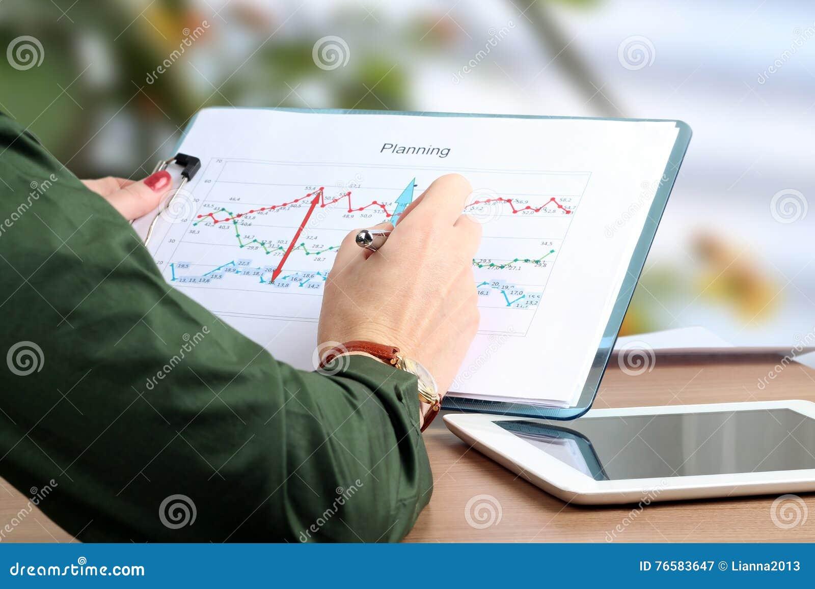 Młody bizneswoman pracuje w biurze, siedzący przy jej biurkiem, analizujący dane w grafika, wskazuje piórem