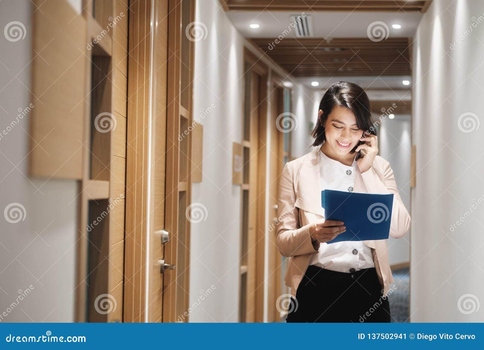 Młody bizneswoman Pracuje W Pieniężnym Agencyjnym mówieniu Na telefonie komórkowym