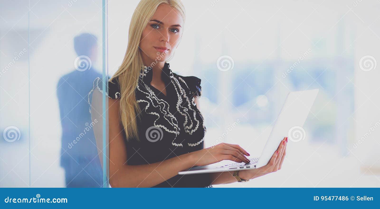 Młody bizneswoman trzyma laptop, stoi na biurze